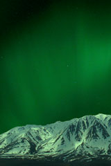 green northern lights above Alaska Range mountain